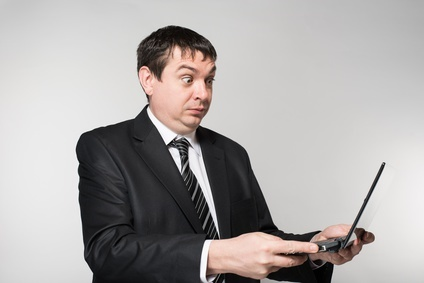 surprised businessman holding a laptop