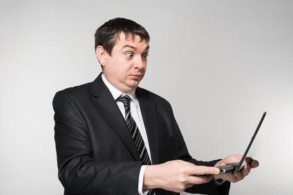 surprised businessman holding a laptop