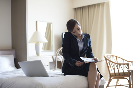 Business Woman talking on the smartphone in a room of the hotel